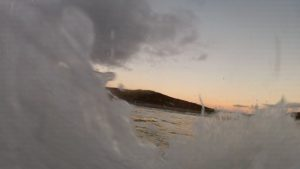 November bodysurf, silhouette of Newgale through the waves